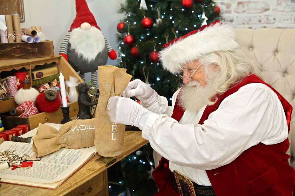 Santa tying ribbons on gifts
